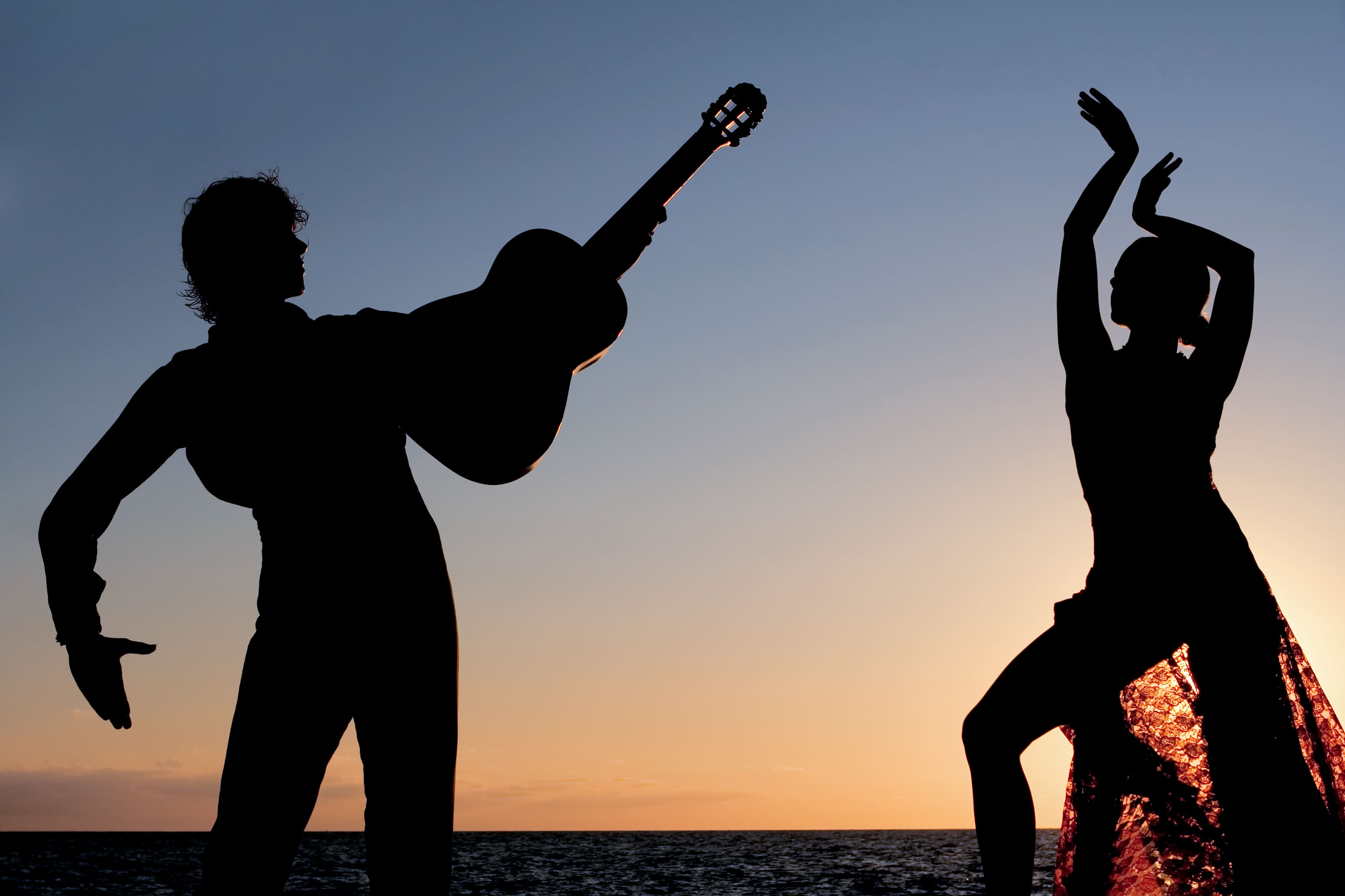 silhouette of spanish dancers dancing outdoors with guitar.